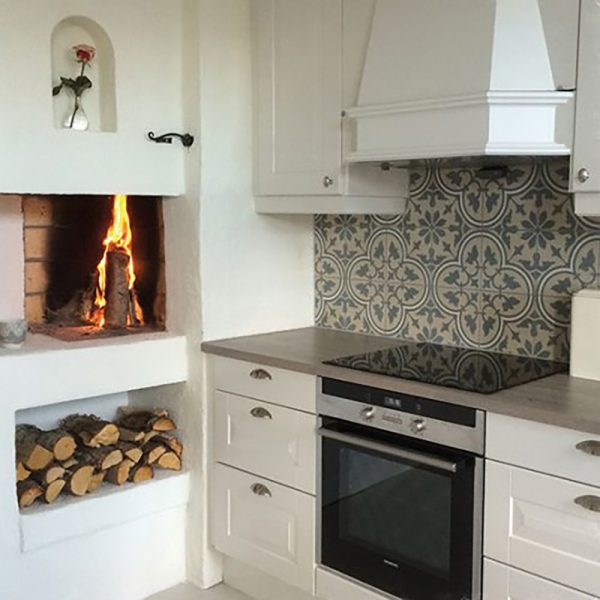Væg i køkken belagt med historiske fliser med Italiensk motiv i blå med hvide kanter