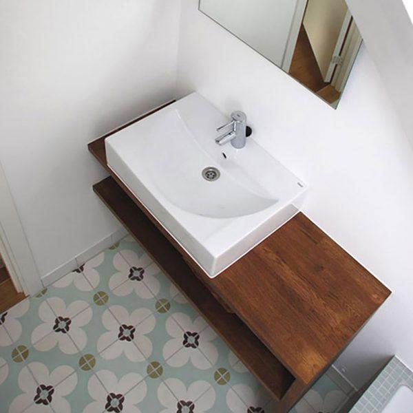 Historiske fliser med motiv fra portugalv på gulv foran håndvask på badeværelse