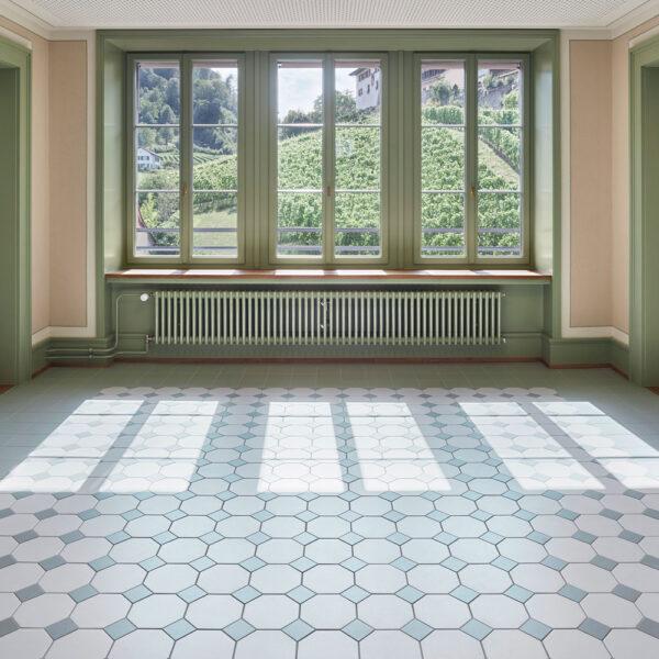 Hårdtbrændt keramisk flise i ottekant og med lille indlægger lagt i rum i farverne mint og hvid