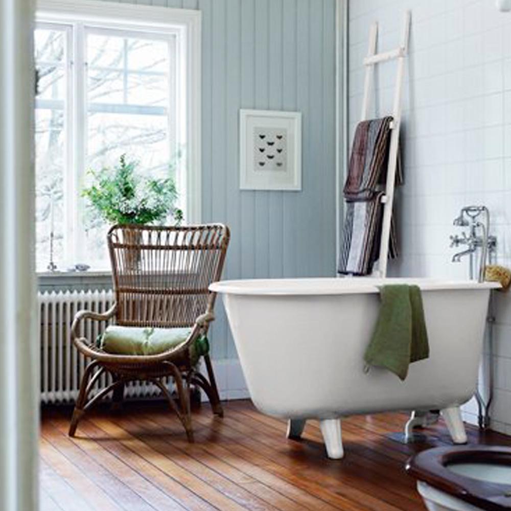 badeværelse med mørkt trægulv, badekar på fødder og lysblå panelvæg